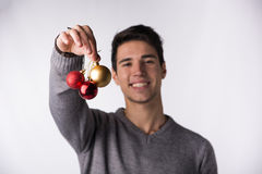 Attractive young man holding Christmas tree balls Royalty Free Stock Image