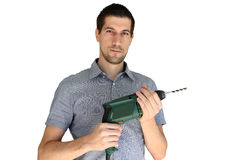 Attractive young man holding an electric drill. A portrait of attractive casual young man holding an electric drill Stock Photo