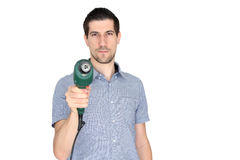 Attractive young man holding  an electric drill. A portrait of attractive young man holding  an electric drill Royalty Free Stock Photo