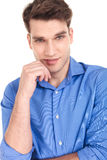 Attractive young man holding one hand to his chin. Royalty Free Stock Photo