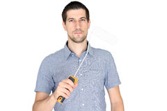 Attractive young man holding a paint brush. A portrait of attractive young man holding a paint brush Stock Photography