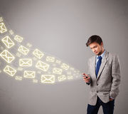 Attractive young man holding a phone with message icons Royalty Free Stock Photo
