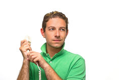 Attractive young man holding telephone. Good looking guy holding the line on phone Royalty Free Stock Image