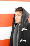 Attractive young man in hoodie against white and orange wall Stock Image