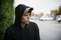 Attractive young man with hoodie and baseball cap in city. Street, sad or thinking Stock Photos
