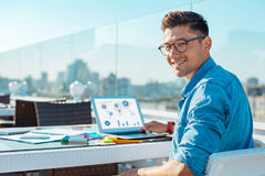 Attractive young man at laptop smiling for camera Stock Photography