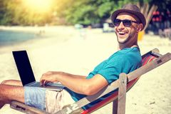 Attractive young man with laptop working on the beach. Freedom,. Remote work, freelancer, technology, internet, travel and vacation concepts royalty free stock photography