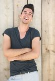 Attractive young man laughing with arms crossed Royalty Free Stock Photography