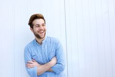 Attractive young man laughing with arms crossed Stock Photography