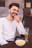 Attractive young man laughing seated at a terrace. Beer and snacks Stock Images