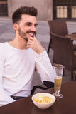 Attractive young man laughing seated at a terrace. Beer and snacks Stock Photos