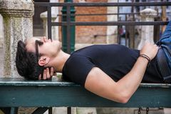 Attractive young man laying down on wood bench Royalty Free Stock Photography