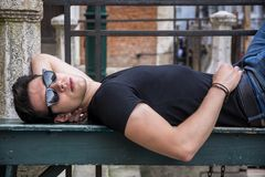 Attractive young man laying down on wood bench Stock Photography