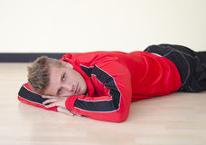 Attractive young man laying on the floor wearing gym suit Stock Photo