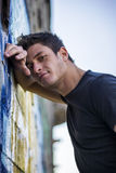 Attractive young man leaning against graffiti wall Stock Image