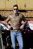 Attractive young man in leather jacket and jeans in front of old train. Wearing sunglasses Royalty Free Stock Photography