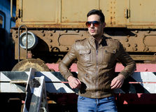 Attractive young man in leather jacket and jeans in front of old train Royalty Free Stock Photography