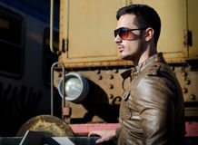 Attractive young man in leather jacket and jeans next to old train. Attractive young man in leather jacket and jeans in front of old train wearing sunglasses Stock Image