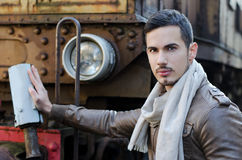 Attractive young man in leather jacket and jeans next to old train. Looking at camera Stock Photo