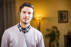 Attractive young man listening to music on headphones at home. Looking at camera, serious Royalty Free Stock Image