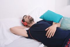 Man listening to music in bed. Attractive young man listening to music and relaxed in bed. Indoors Stock Photos