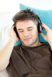 Attractive young man listening to music on a sofa Royalty Free Stock Images