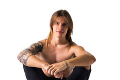 Attractive young man with long hair shirtless, sitting, isolated Royalty Free Stock Photography