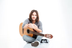 Attractive young man with long hair sitting and holding guitar Stock Photo