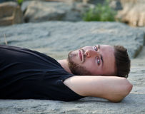 Attractive young man lying on his back on a rock, looking in camera Stock Image