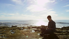 Attractive young man is meditating while sitting on a seashore with his laptop. But then he is starting to typing something stock footage