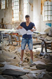 Attractive young man in messy office or working place. Tearing up paper sheets Stock Images