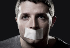 Attractive young man with mouth sealed on duct tape to prevent him from speaking Stock Images