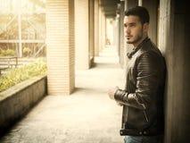 Attractive young man in narrow columns corridor outdoors stock image