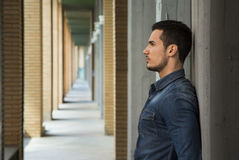 Attractive young man in narrow columns corridor outdoors Royalty Free Stock Photo