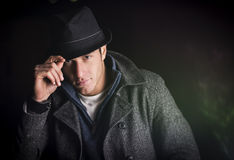 Attractive young man at night, wearing winter coat and fedora hat Stock Images