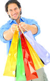Attractive Young Man Offering Shopping Bags. Happy young male caucasian offering shopping bags to viewer. isolated on white Stock Image