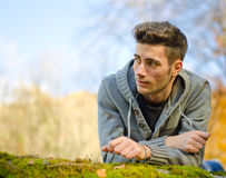 Attractive young man outdoors in nature lying on moss. Handsome young man outdoors in nature lying on moss, large copyspace royalty free stock images