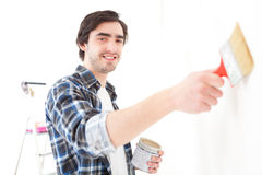 Attractive young man painting a wall in his new flat Royalty Free Stock Photos