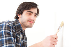 Attractive young man painting a wall in his new flat Stock Images