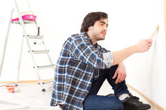 Attractive young man painting a wall in his new flat Stock Photos