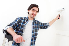 Attractive young man painting a wall in his new flat Stock Image