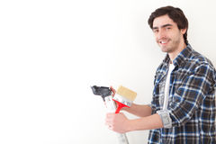 Attractive young man painting a wall in his new flat Royalty Free Stock Photography