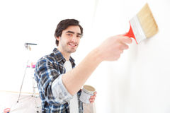 Attractive young man painting a wall in his new flat Stock Photo