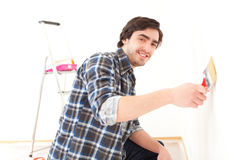 Attractive young man painting a wall in his new flat Royalty Free Stock Images
