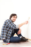 Attractive young man painting a wall in his new flat Royalty Free Stock Photo