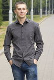The attractive young man in park, keeps hands in pockets Royalty Free Stock Image