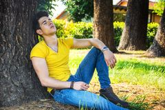 Attractive young man in park resting against tree Stock Photos