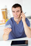 Attractive young man phoning and holding a card Royalty Free Stock Photo