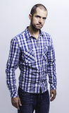 Attractive young man in a plaid shirt. Young man in a plaid shirt, looking straight at the camera.  on white background Stock Image