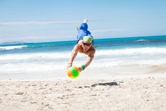 Attractive young man playing volleyball on the beach Stock Photos